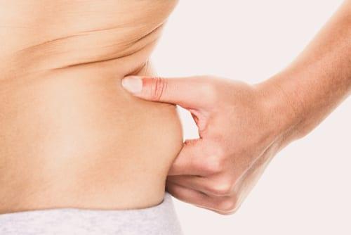 love handle woman pinching fat on hips around waist-img-blog