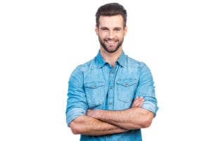 Confident young handsome man in jeans shirt keeping arms crossed and smiling while standing