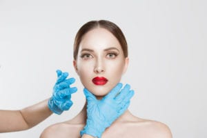 Closeup portrait doctor hands with gloves touching woman face chin lips chin want to change her form do plastic surgery-img-blog